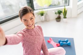 Happy selfie at home Asian young woman smiling training bodyweight exercises on exercise mat in living room of apartment taking mobile phone photo during workout.