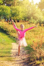 Beautiful Teen Girl  Is Dancing Outside At  The Field At Summer Sunset