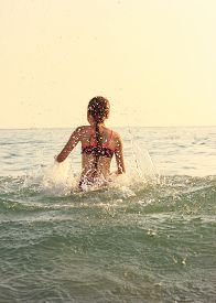Beautiful Teen Girl Playing In Sea Waves. Jump Accompanied By Water Splashes. Summer  Day, Happy Chi