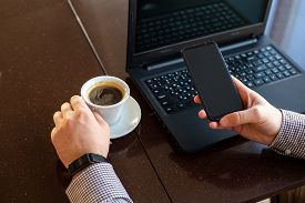 Remote Work. Man Using Laptop, Holding Smart Phone For Business Work Or Study In Smart Watch Drink C
