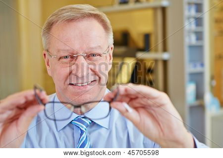 Elderly man as optician holding new glasses