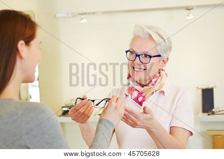 Senior optician giving new glasses to female customer