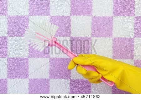 Toilet brush in hand on tile wall background