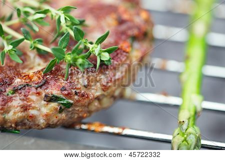 food meat -  burgers on bbq  barbecue grill with asparagus . Shallow dof.