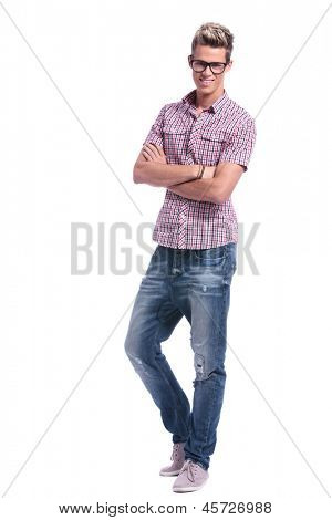 full length photo of a casual young man standing with his hands crossed while looking at the camrea. on white background