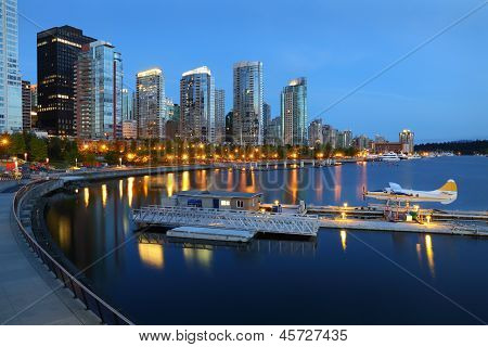 Condominiums at twilight reflecting in the calm water of Coal Harbor in downtown Vancouver. British Columbia, Canada. poster