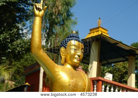 Top of golden statue of the Buddha and small Buddhist temple in the gardens of Matepani Gumba the Buddhist monastery and school just outside Pokhara Nepal. poster