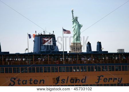 NEW YORK - MAY 17: The Staten Island Ferry John F. Kennedy passes by the Statue of Liberty on May 17, 2013 in New York.