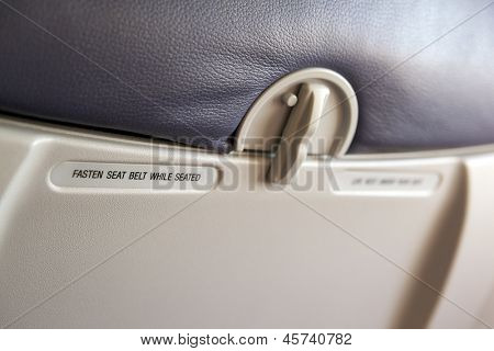 inside airplane seat, focusing with the warning label of