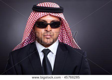 wealthy arabian businessman wearing sunglasses on black background