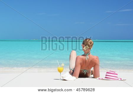 Girl with a glass of orange juice on the beach of Exuma, Bahamas poster