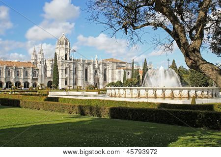 The Mosteiro or monastery dos Jeronimos displaying Manueline architecture with fountain from Praca do Imperio gardens Portugal poster