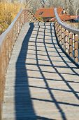 a bridge in bright sunlight with the balustrade throwing a shadow poster