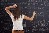 Young woman looking at math problem on blackboard poster