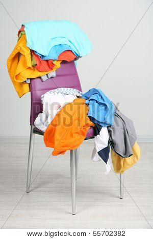 Heap of  clothes on color chair,  on gray background poster