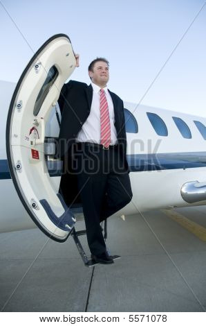 Businessman Standing On The Steps Of Corporate Jet