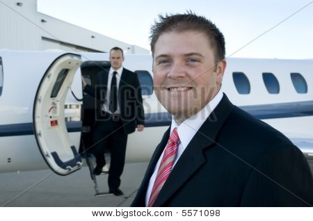 Businessmen Standing In Front Of Corporate Jet