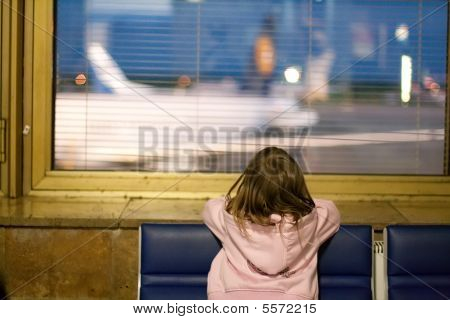 Little Girl At The Window In Airport At Night.