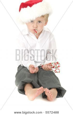 Cute Toddler Wearing Santa Hat Eats Candy Cane