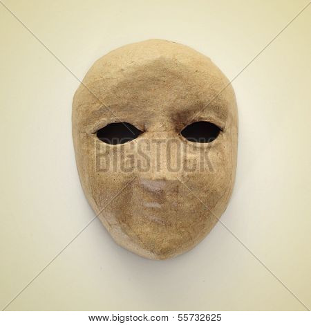picture of a papier-mache mask on a beige background, with a retro effect