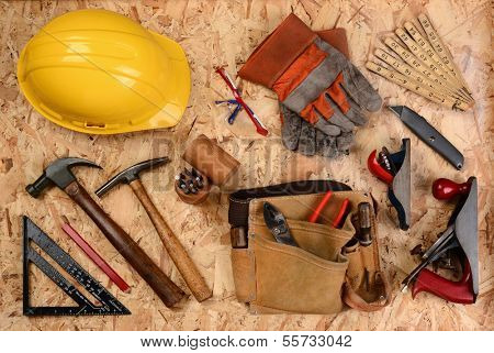 Overhead view of construction equipment and tools laid out on a sheet of plywood. Items include, hard hat, gloves, hammer, square, block planes, ruler, goggles and more. Horizontal format.