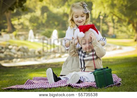 Sweet Little Girl Tries to Put A Santa Hat On Her Reluctant Baby Brother Outdoors at the Park.