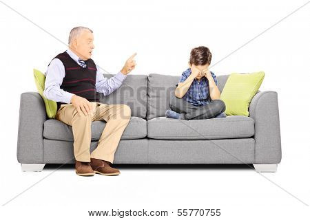 Angry grandfather shouting at his nephew, seated on a sofa, isolated on white background