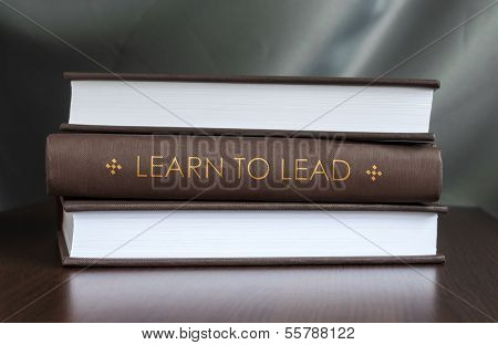 """Books on a table and one with """"Learn to lead"""" cover. Book concept. poster"""
