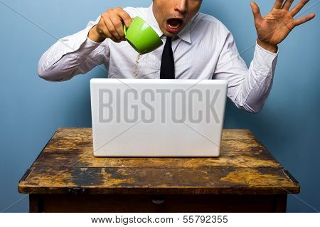 Clumsy Businessman Spilling Coffee On His Laptop Computer