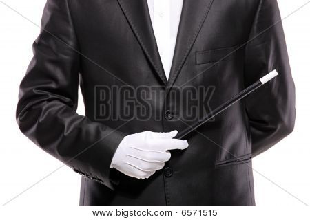 A magician in a suit holding a magic wand