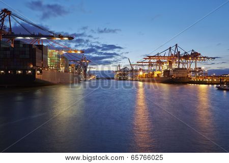Container Vessel At Terminal In Harbor In The Evening