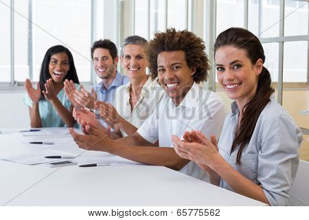 Business people clapping and smiling at camera in the office