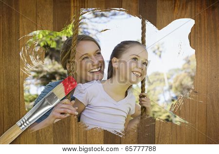 Composite image of mother and daughter in the park against wooden surface with paintbrushes poster