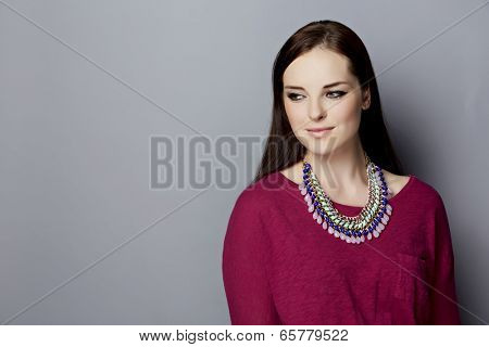 Portrait of a  young woman, with long brunette hair, on gray studio background, wearing pink purple top and bright statement necklace with space for text