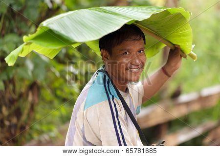 BAAN LOOK KAO LAM, THAILAND, NOVEMBER 19 : portrait of a Lahu tribe man using a banana tree leaf as an umbrella, in the village of Baan Look Kao Lam, north Thailand on November 19, 2012