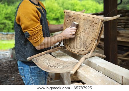 poster of Restoration, removing paint from antique chair with sandpaper