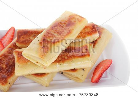 russian food - heap of sweet pancake filled with cottage cheese with strawberry served on white plate isolated over white high resolution hidef