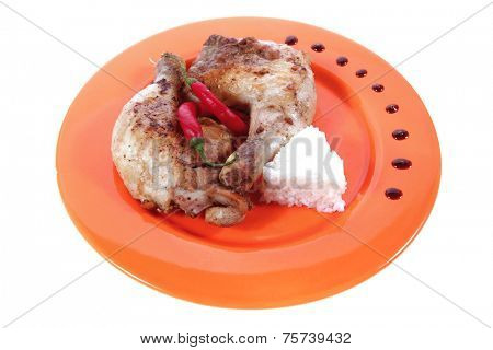 grilled chicken thighs on orange plate with white rice and red hot chili pepper isolated over white background high resolution