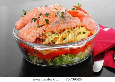 fresh fried natural pink salmon on italian traditional tagliatelle backed with tomato and vegetables served over black wooden table high resolution hidef