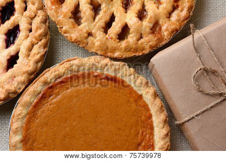 High angle closeup of three fresh baked holiday pies and a plain paper wrapped package. The traditional American desserts - Pumpkin, Cherry and Apple pie are Thanksgiving staples. Horizontal format.