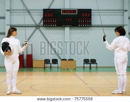 Young woman fencer and her trainer