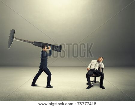 dissatisfied boss holding big hammer and screaming at lazy worker. photo in the dark room