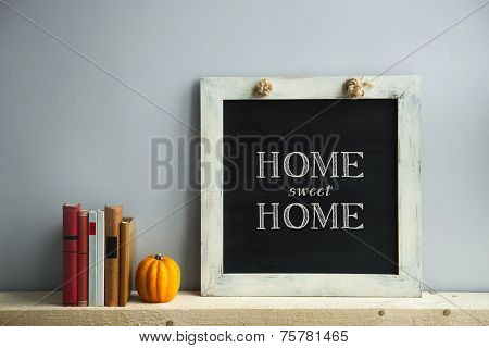 Chalkboard Frame On The Grey Wall With Books And Pumpkin Home Sweet Home