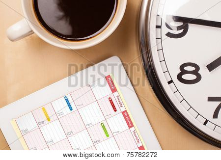 Workplace with tablet pc showing calendar and a cup of coffee on a wooden work table close-up poster