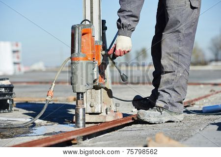 concrete boring with industrial drilling machine on building construction site