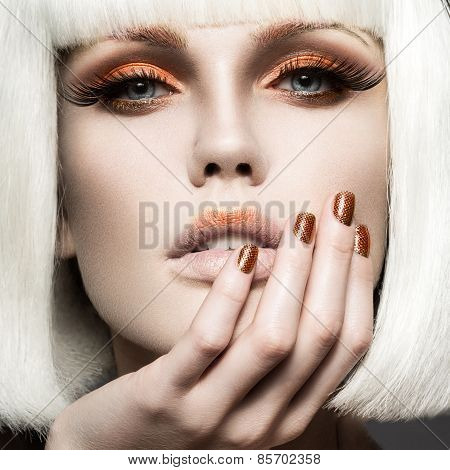 Beautiful girl in a white wig, with gold makeup and nails. Celebratory image. Beauty face.