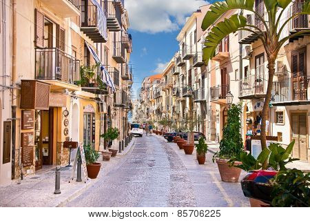CEFALU, SICILY - SEPTEMBRE 16,2014: Old mediterranean steet with tourist in Cefalu, medieval city of Sicily, Italy.It situated on the northern coast of Sicily, about 70 km from Palermo.