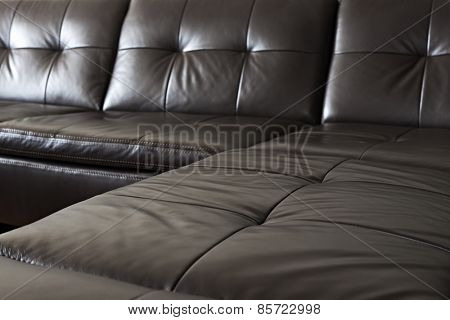 Closeup of luxurious expensive black leather couch