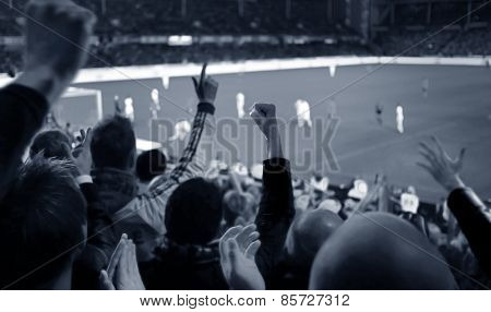 Fans excited at a football game, selective focus on fans with hands raised