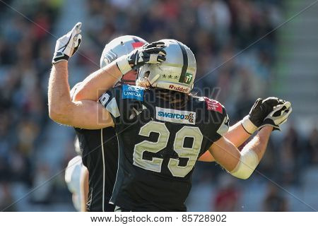 INNSBRUCK, AUSTRIA - MARCH 29, 2014: QB John Van Den Raadt (#7 Raiders) and RB Andreas Hofbauer (#29 Raiders) celebrate a touchdown in an AFL football game.